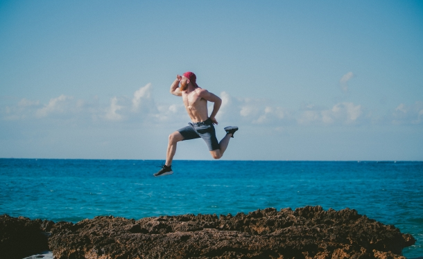 Man jumping on rocks by the ocean.jpg