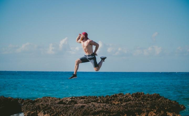 Man jumping on rocks by the ocean.jpg